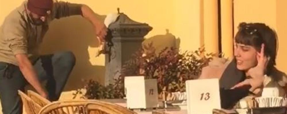 Si lava i piedi alla fontanella  Davanti ai turisti seduti al bar