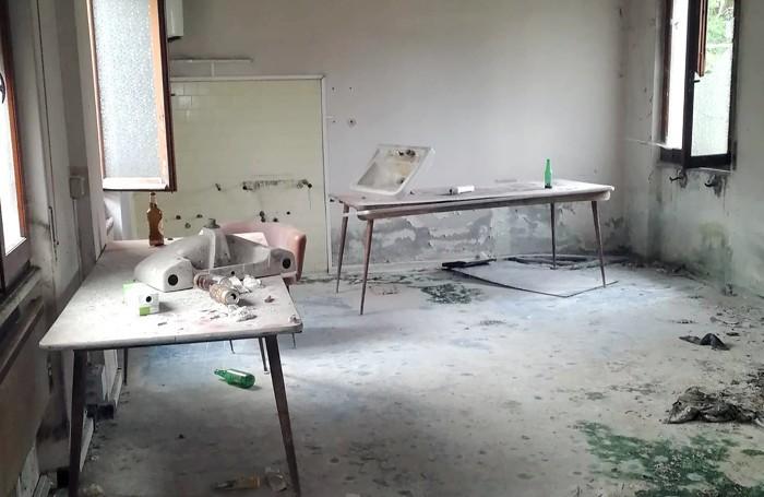 Bottiglie e lattine abbandonate e rotte insieme agli arredi in un ufficio della ex Spreafico